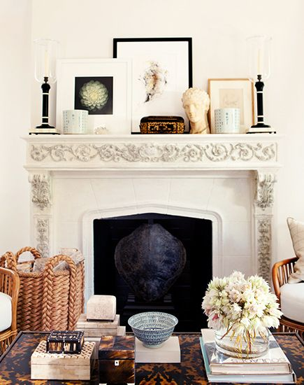 white fireplace with several framed images leaning on the mantel in a living room