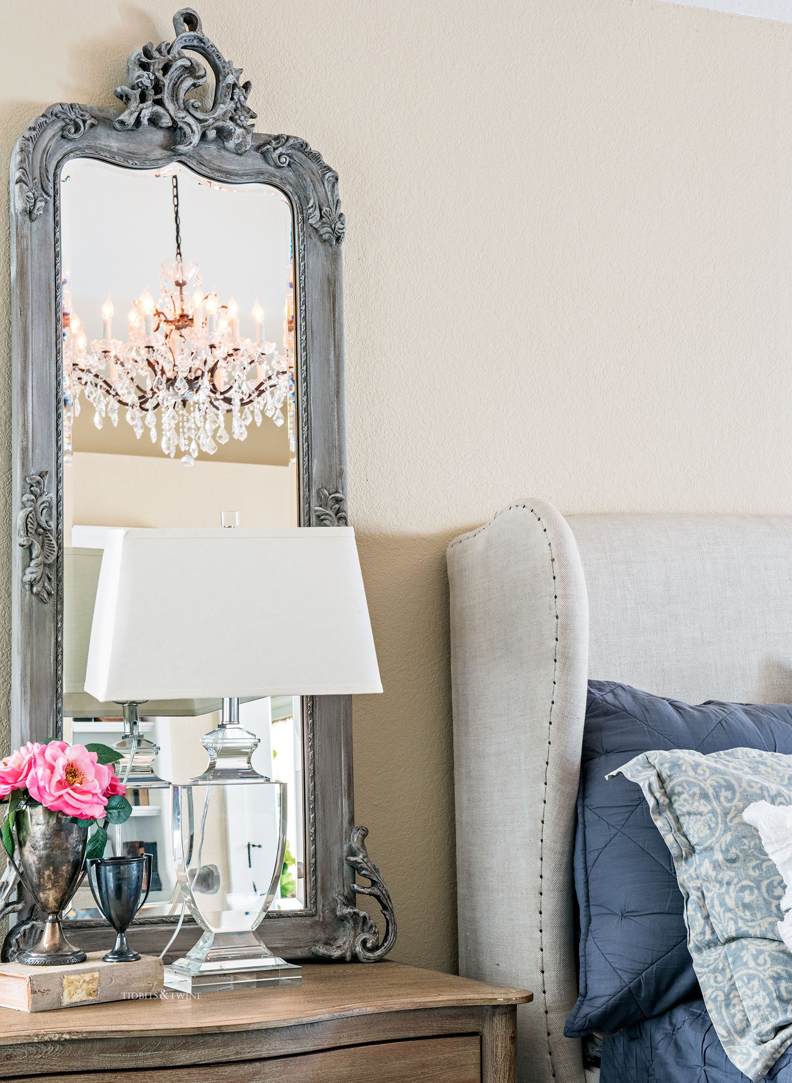 A French master bedroom nightstand with gray mirror and a crystal lamp on bedside table next to linen wingback bed