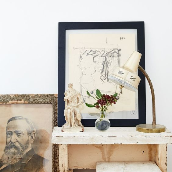 small table with framed sketch leaning on top and portrait leaning on floor next to it