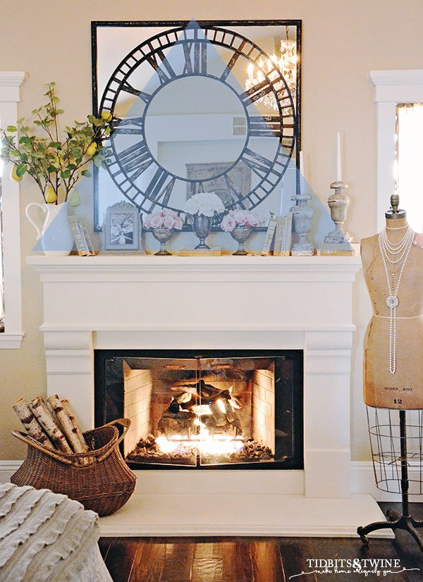 Create a triangle of decor above white french fireplace mantel next to antique dress form
