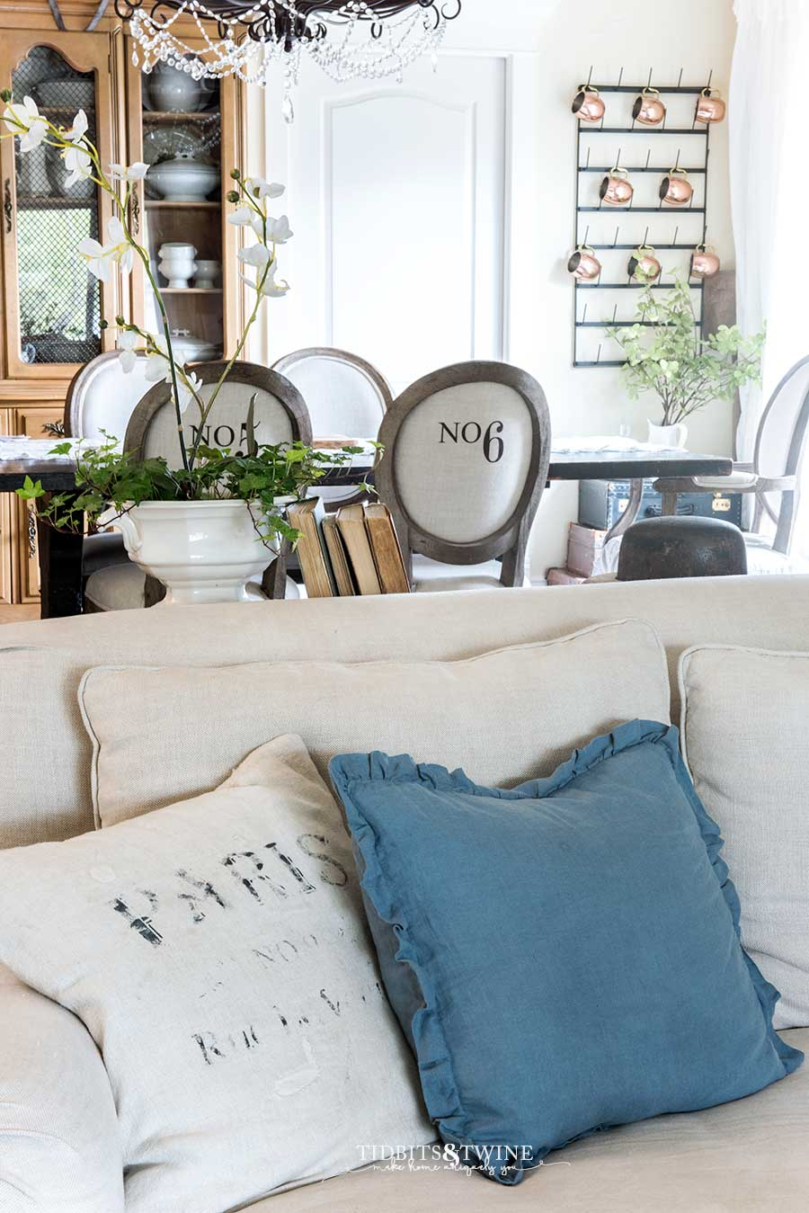 Grain sack pillows on a linen slipcovered sofa. Numbered dining chairs.