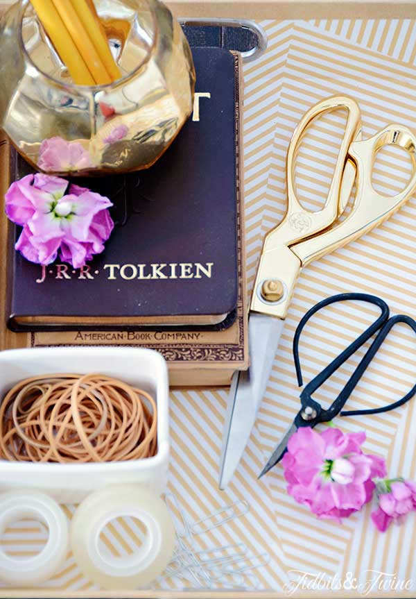 closeup of gold scissors and desk supplies with purple flowers
