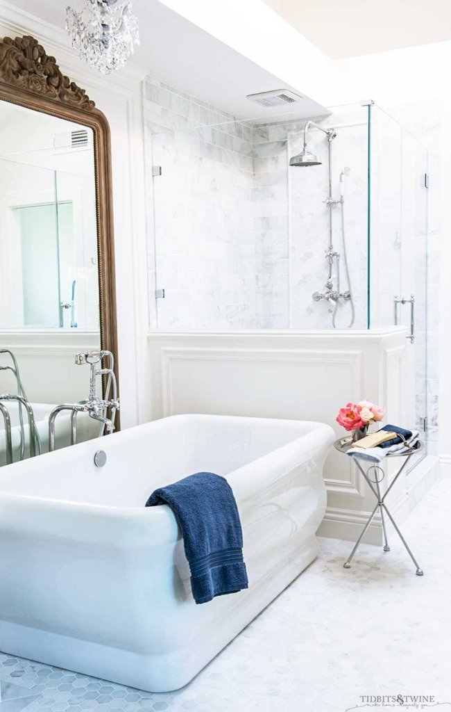 Elegant french master bathroom with freestanding tub next to shower with pony wall and white trim
