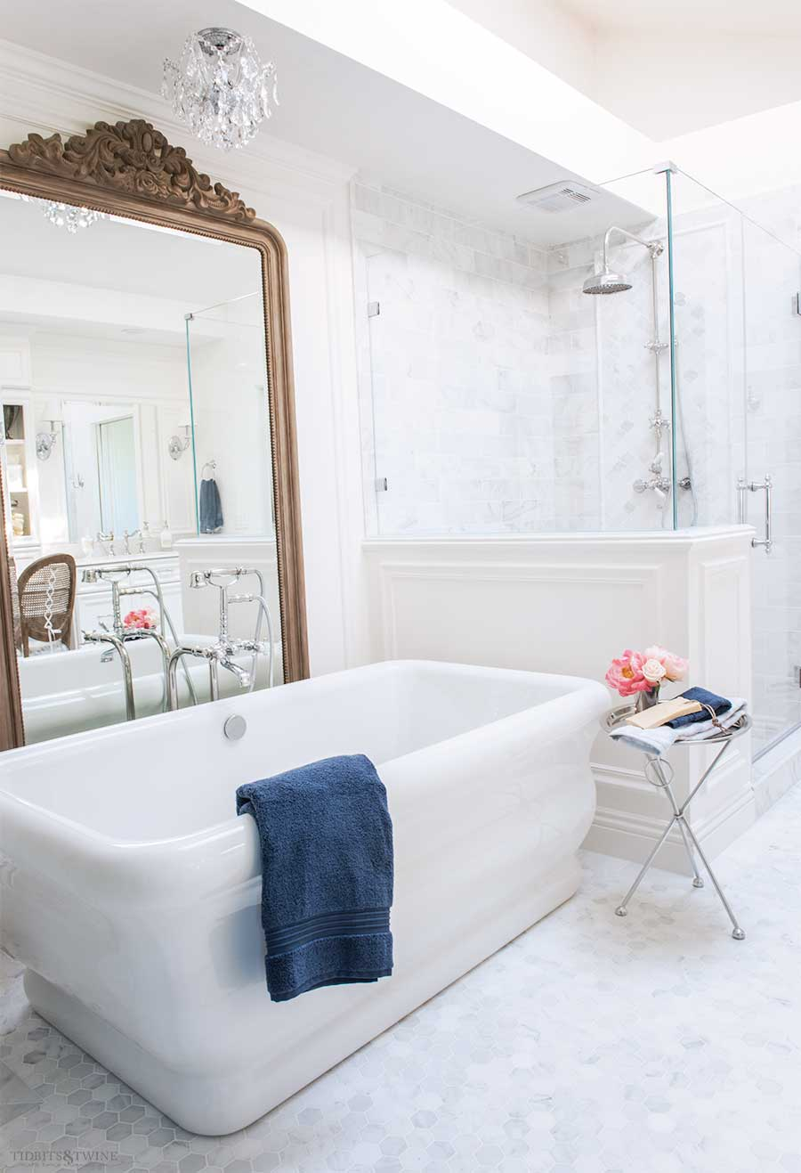 Elegant marble bathroom with freestanding tub and ornate french wood floor mirror behind the tub next to a shower pony wall