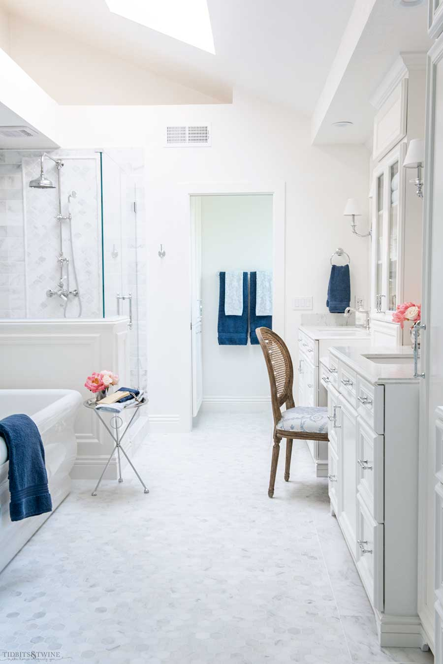 French elegant master bathroom with white marble floor freestanding tub shower pony wall and blue accents