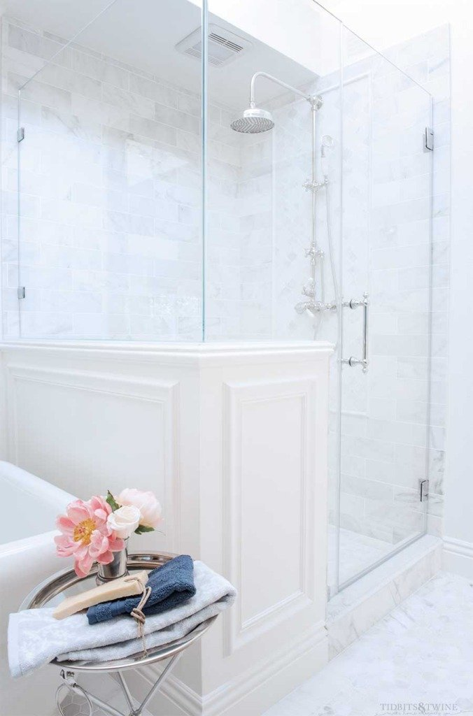 French master bathroom with carrara shower pony wall next to freestanding tub
