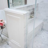 Shower pony wall with carrara marble bench and niche