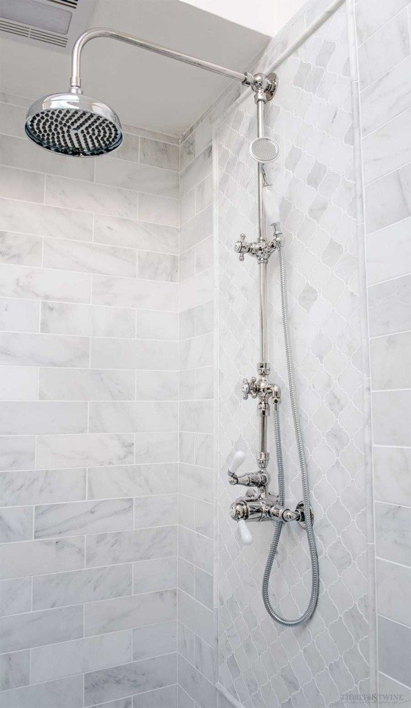 Sigma exposed pipe shower with marble subway tile in French elegant bathroom