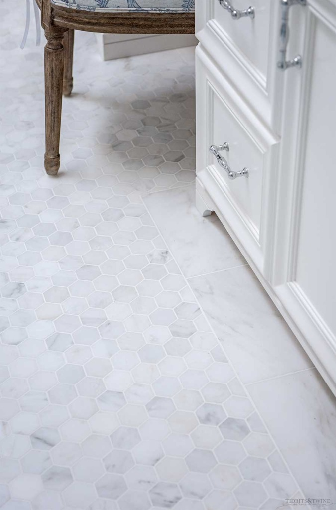 Venato Carrara marble hexagon floor with subway tile border in french elegant master bathroom next to custom white vanity cabinets