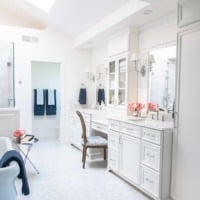French elegant white marble master bathroom with double vanities and freestanding tub
