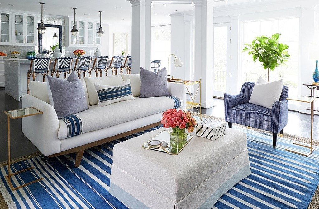 Great room with white sofa and blue stripe rug and white walls