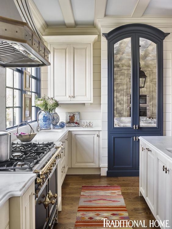 Traditional kitchen with white cabinets and blue built in refrigerator with mirrored doors