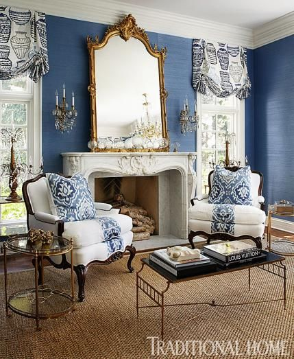 french living room with solid blue grasscloth wallpaper and gold mirror