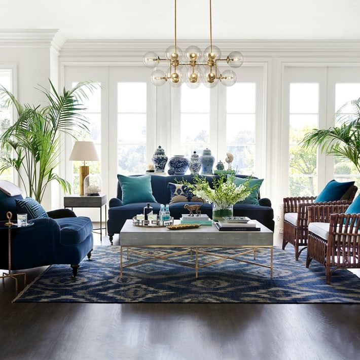 Blue velvet sofa and chair with white and gold coffee table and ikat rug