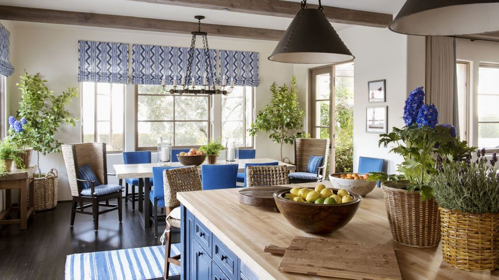 Kitchen with blue cabinets and butcher block countertop and blue chairs