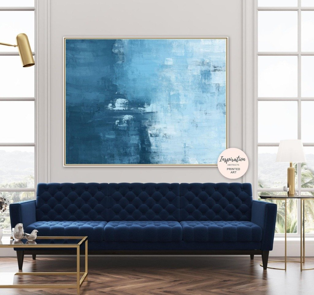 Modern blue abstract downloadable artwork above a blue tufted sofa