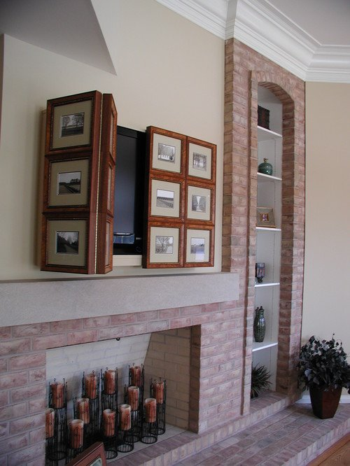 TV above fireplace covered by picture frames