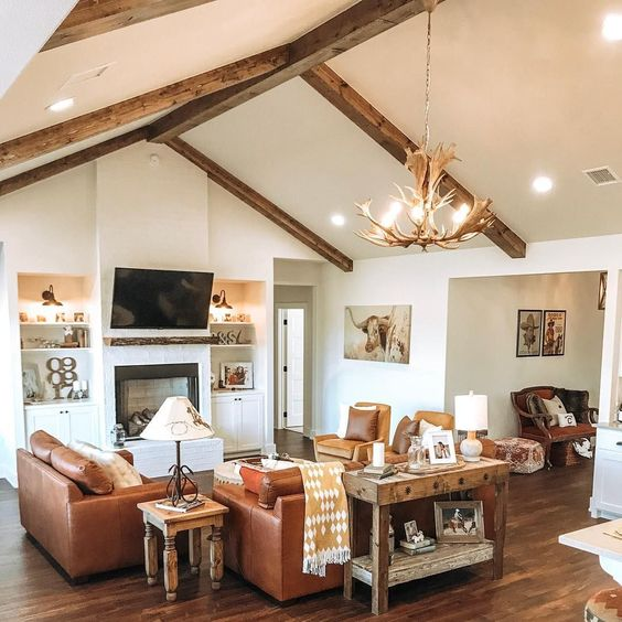 A Western style family room with leather sofas and rustic wood and antler light fixture