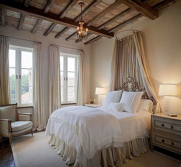 European bedroom with canopy above bed and wooden beam ceiling
