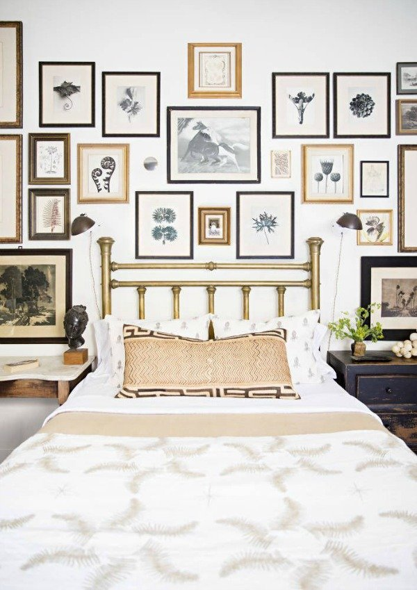 Collected gallery wall above the bed