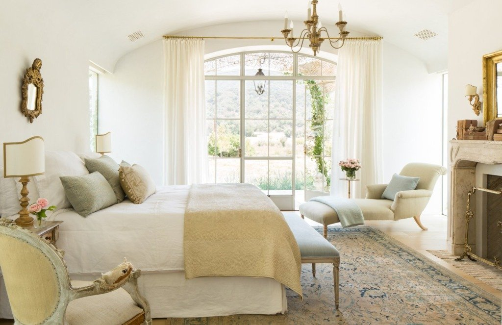 European bedroom with white walls and gold accents and stone fireplace mantel