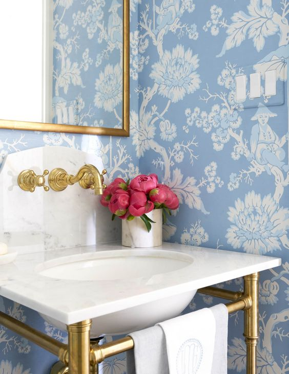 Bathroom with blue floral wallpaper and gold accents