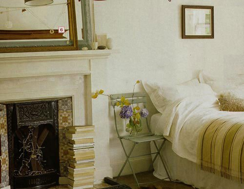 Vintage folding chair as a nightstand next to a bed and a fireplace with a stack of books
