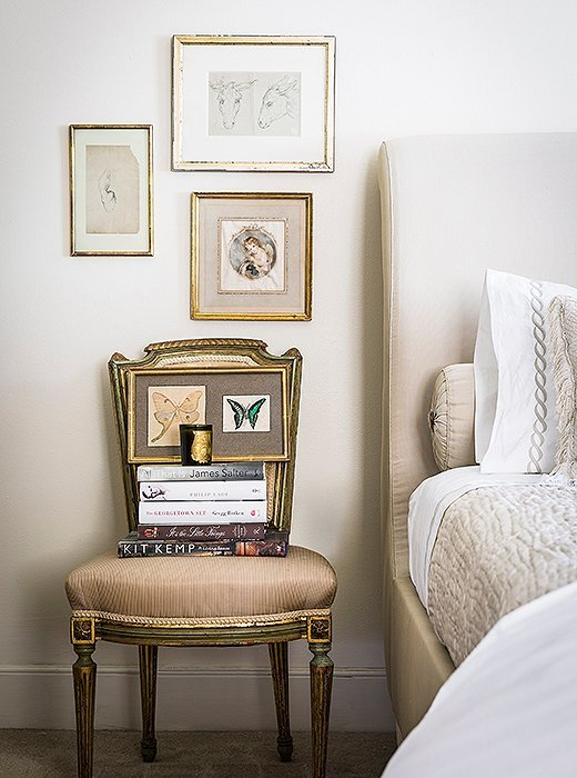 Antique French used as a nightstand stacked with books and art next to upholstered bed