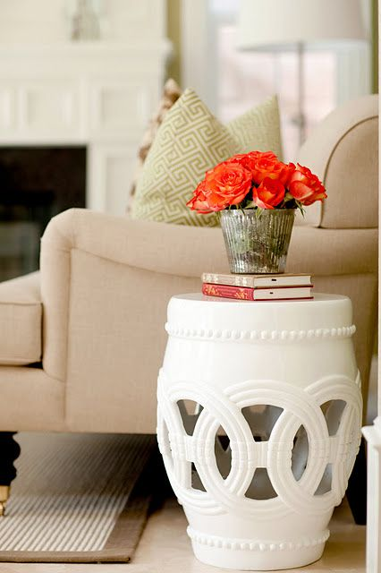 White garden stool used as a side table next to a beige sofa