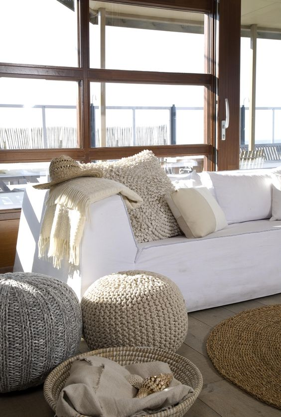 Grouping of poufs used as a side table next to a white sofa in a living room