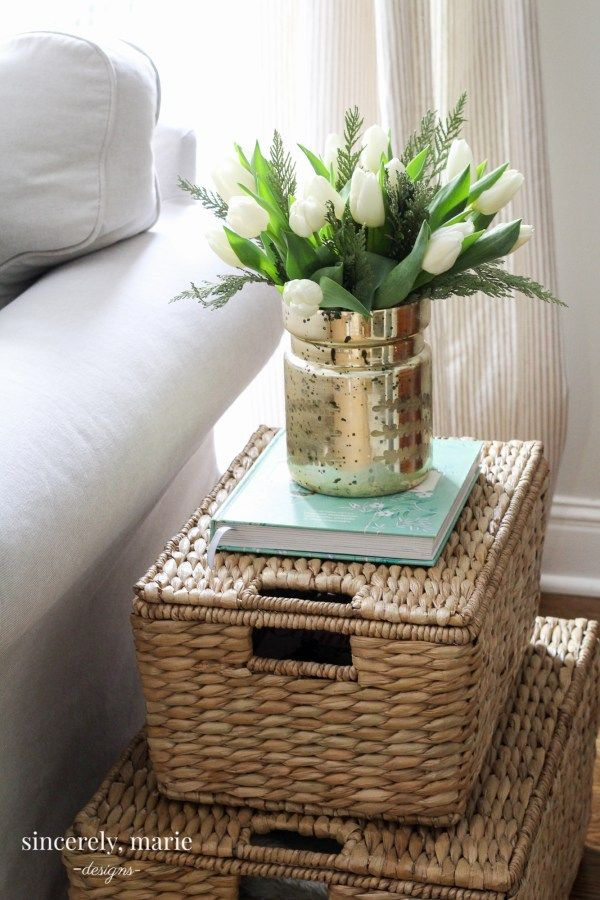 Lidded seagrass baskets stacked as a side table next to a white sofa with a vase of tulips