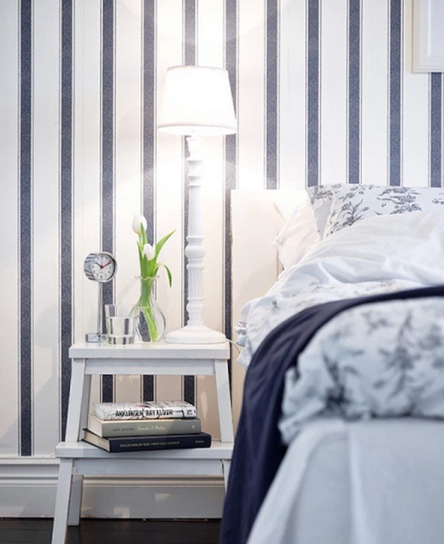 White step stool used as a nightstand next to a blue and white bed with stripe wallpaper