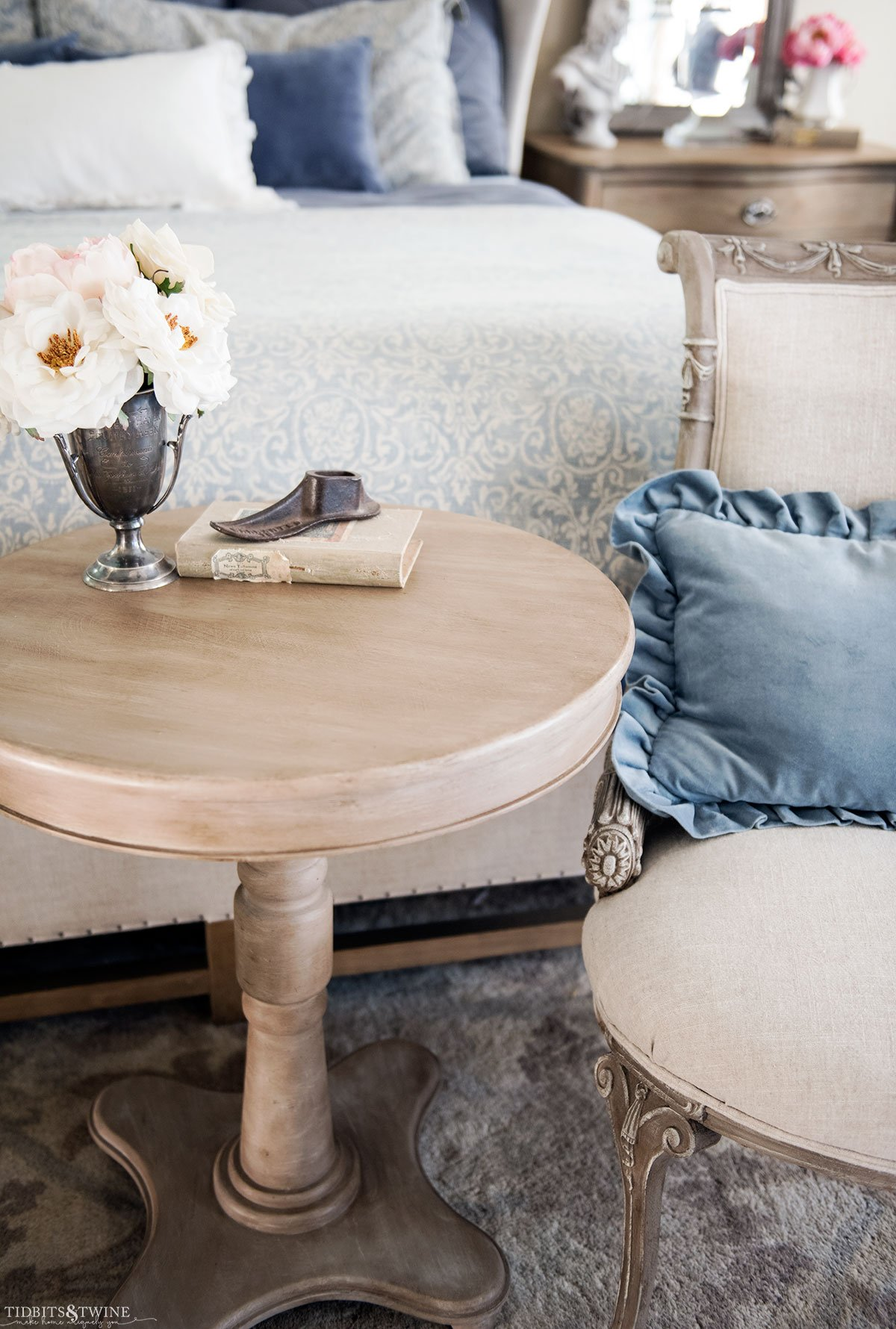 DIY faux wood table and french chairs at end of bed with blue ruffle pillow