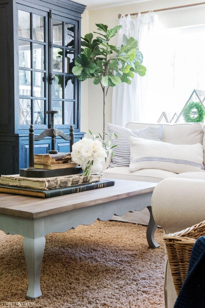French country coffee table in family room with black cabinet and fiddle leaf fig