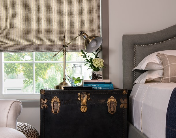 Vintage black trunk as a nightstand with a gold lamp on top