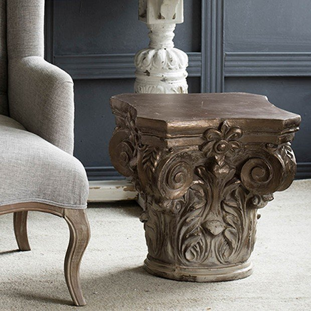 architectural pedestal side table next to french chair
