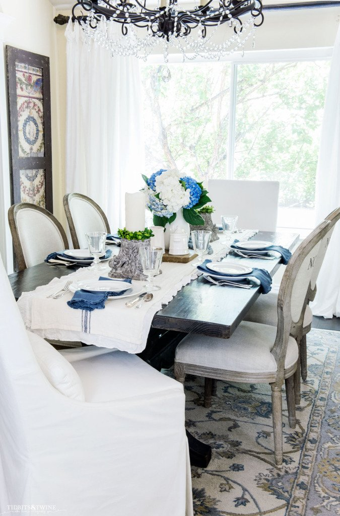 French dining room with blue and white setting and mismatched chairs