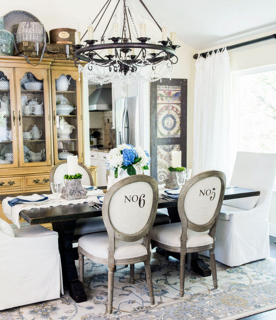 French dining room with numbered side chairs and white slipcovered head chairs