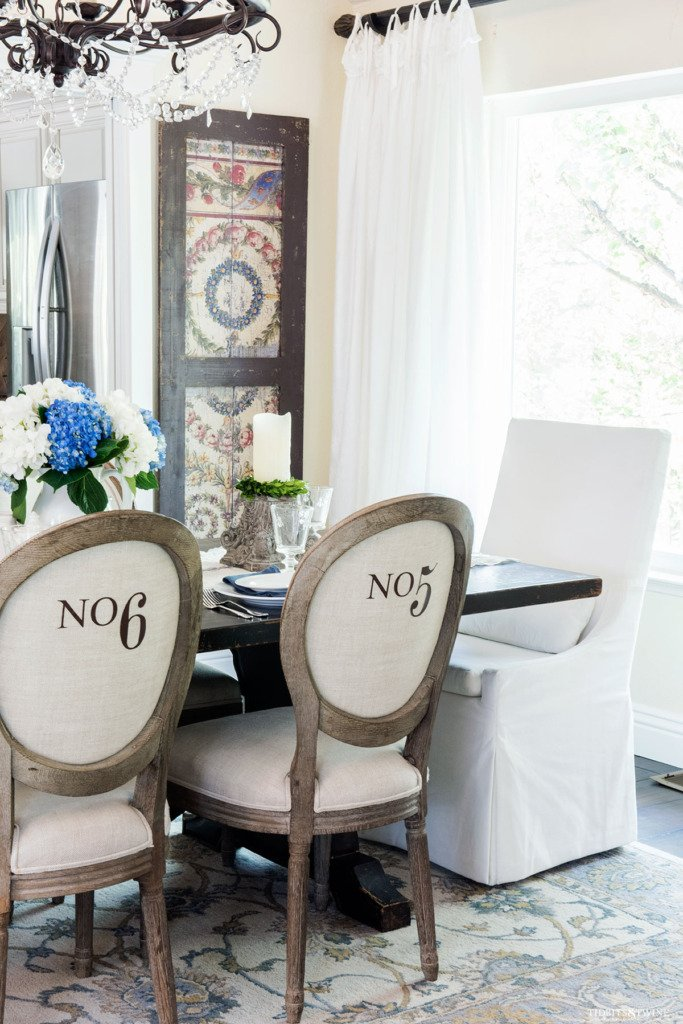 Dining room with round french chairs with numbers on backs and white slipcovered head chair