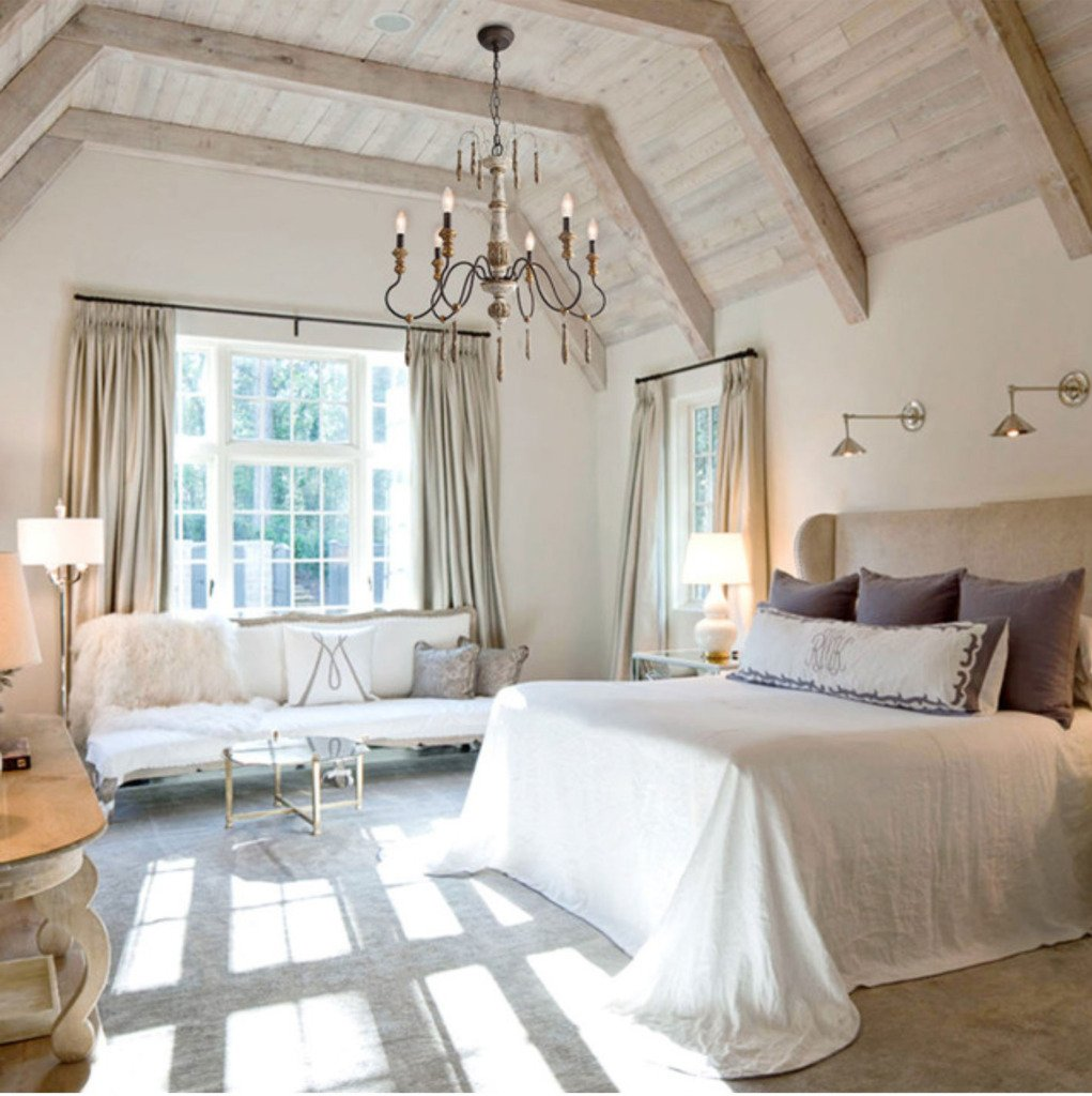 French bedroom with wood ceiling and french country chandelier above the bed