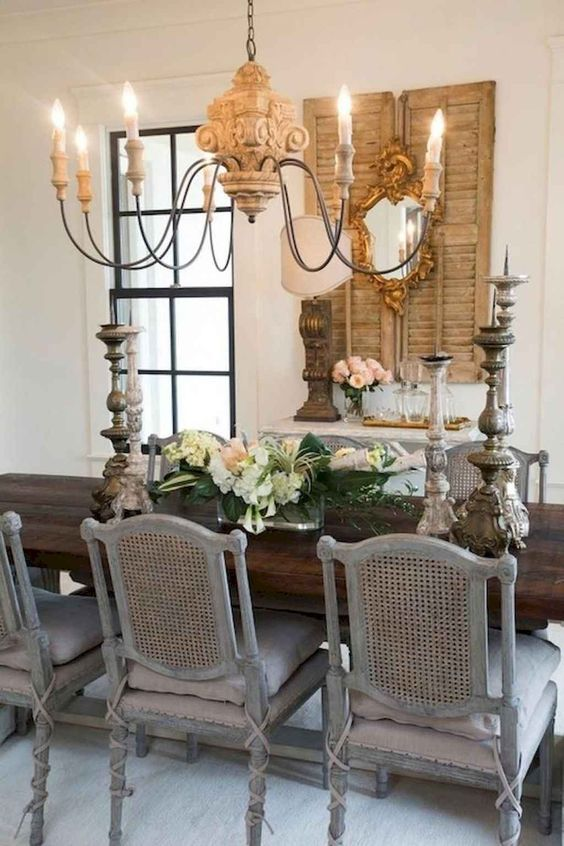 French country dining room with antique chairs and wood carved chandelier