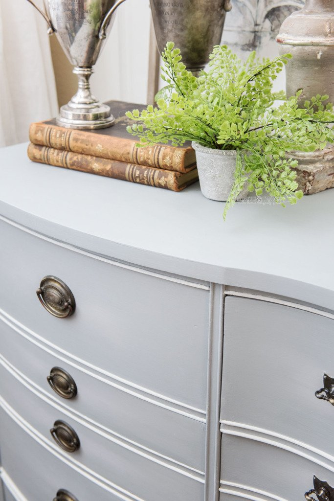 Closeup of antique dresser with gray blue chalk paint with books and trophies on top