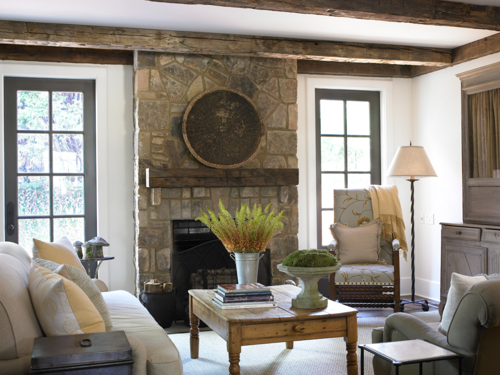 Den with stone fireplace flanked by french doors and beam ceiling