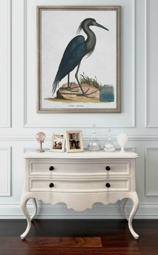 Large artwork image of blue heron hanging above a small chest of drawers