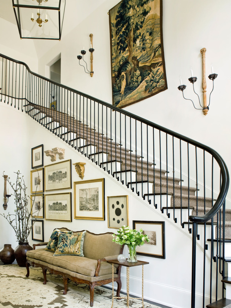 entryway with large staircase vintage gallery wall and french sconces