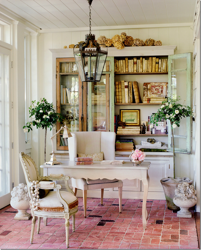 French home office with large bookcase filled with antique books and brick floor