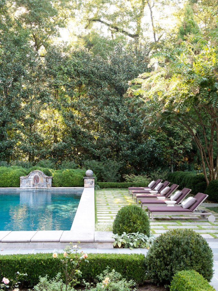 french backyard poor with fountain boxwoods and grass between pavers