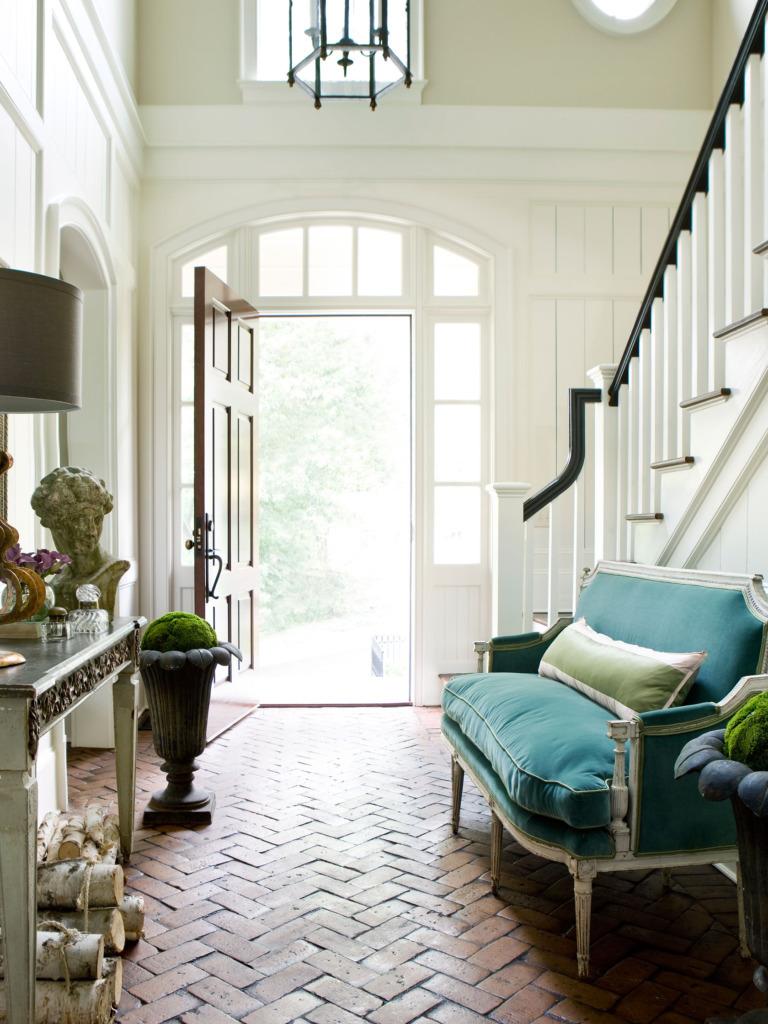 two story entryway with herringbone brick floor and blue velvet settee