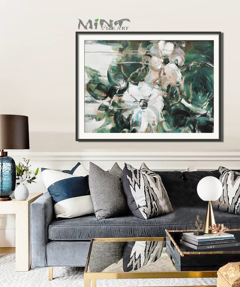 Blue and green abstract art image of flowers hanging above a sofa
