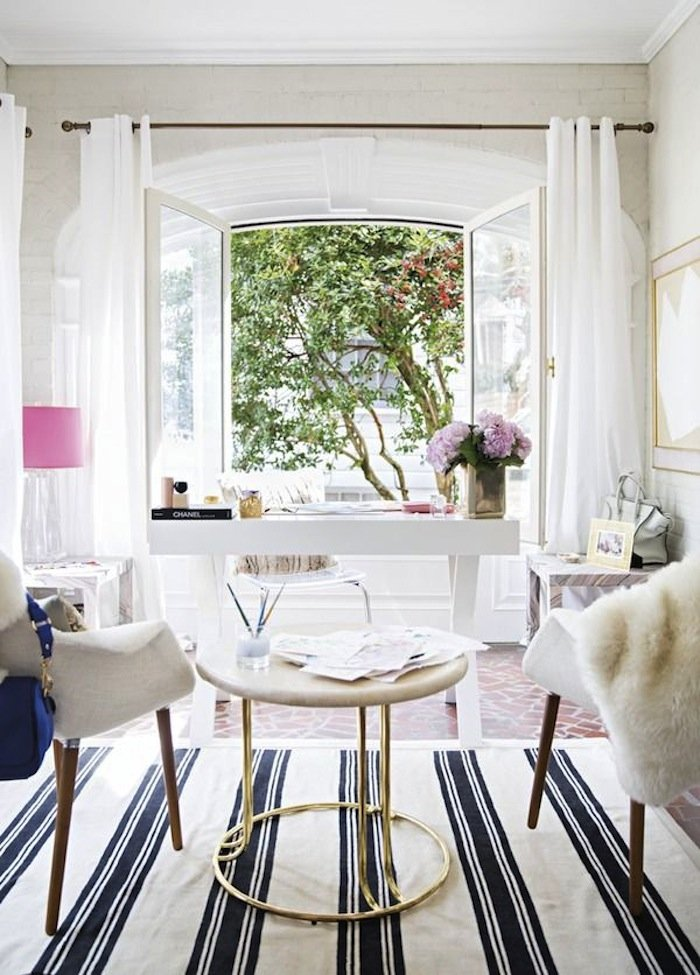 feminine home office with white desk in front of french doors